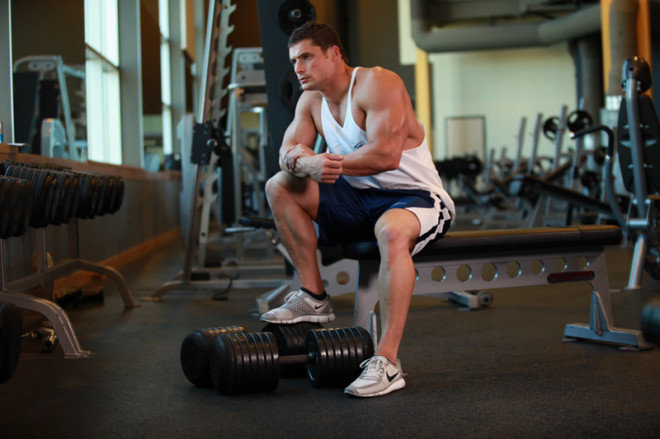 man resting with one foot on weights