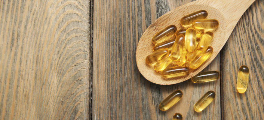 fish oil capsules in a spoon on a wooden background